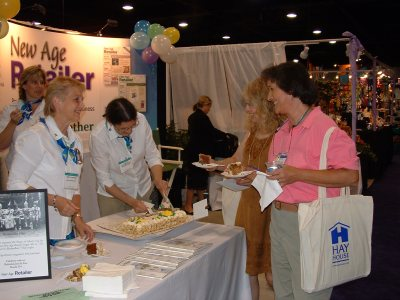Brita greeting retailers at the International New Age Trade Show in June 2004, while Annette MacKenzie, who also has left us now, cuts a piece of cake. (Also: dear Trinka Baron, back left; Lisa Braun Dubbels in the back, making herself at home in our booth and/or using it for storage purposes; and Blair Justice of Crystal Visions, now literally a ways down the street from me where I live in North Carolina, visiting the booth with her ever-present smile.