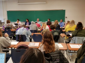Ray Hemachandra moderating a panel at the University of North Carolina Asheville, with autistic adults and autism/disability professionals talking about the value of disabled lives prior to the 2018 Disability Day of Mourning.